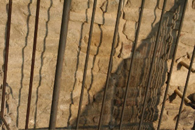 Straight railings casting rippled shadows on a rough stone wall.