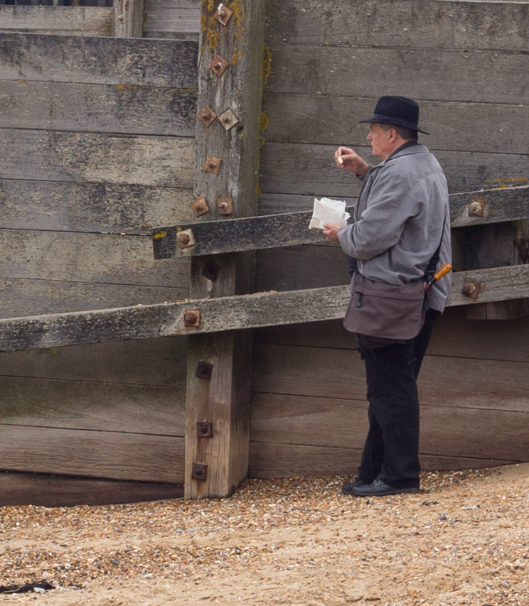 Covert chip-eating on the beach, hiding beside a groyne - but who is he hiding from . . .