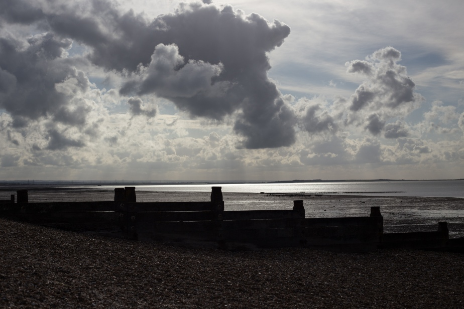 At last by late afternoon the solid grey sky began breaking up and shafts of silvery light played across the sea.