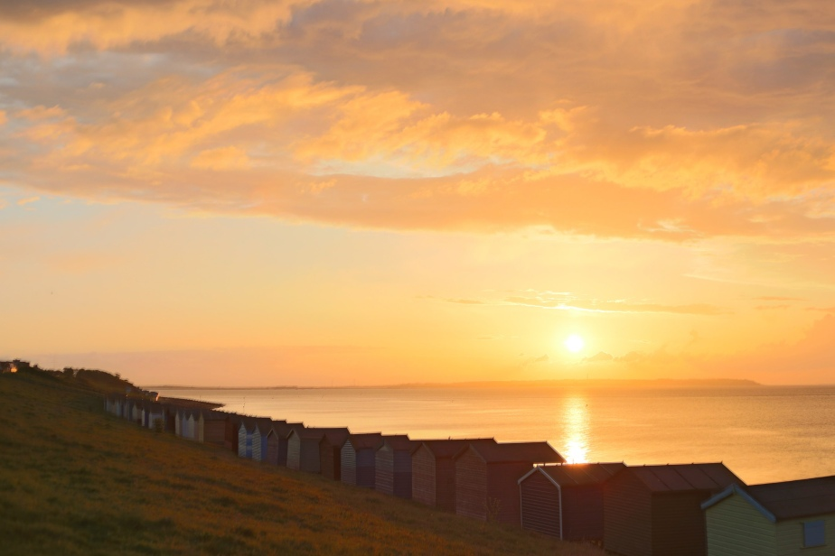 Just before the sun disappeared behind the distant strip of Essex, the view from Tankerton over the huts was  pure colour, the grass turning russet.